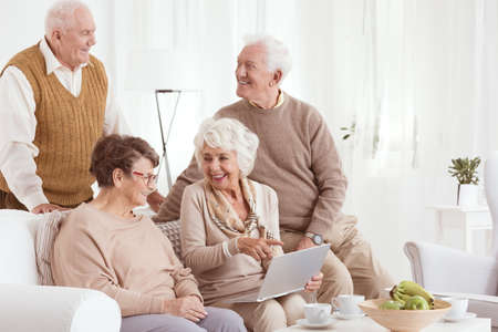 neighborly: Group of elderly people using new technology in retirement club