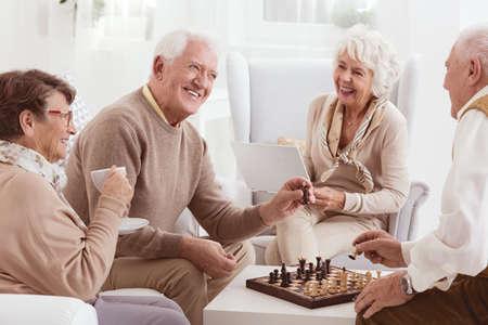 Oude mensen spelen schaak samen in dagverblijf