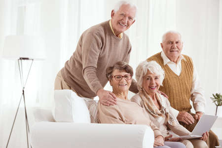 neighborly: Two couple of grandparents meeting together at home Stock Photo