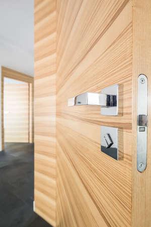 Spacious modern corridor with wooden door and silver handle