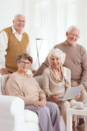 neighborly: Senior friends sitting in living room and using laptop Stock Photo
