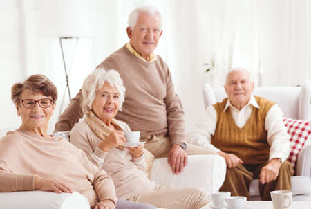 Elderly friends spending tea time together in retirement club Stock Photo