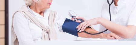 preasure: Doctor measuring elderly patients blood pressure in retirement house Stock Photo