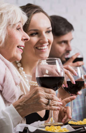 anecdote: Happy elderly mother and daughter with husband drinking red wine during family dinner Stock Photo