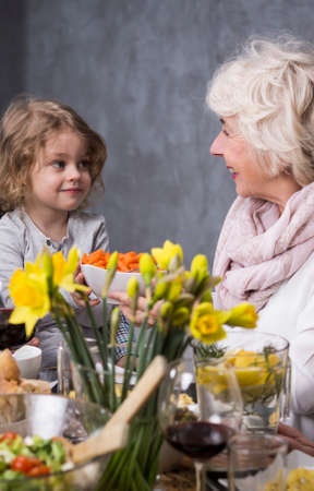 anecdote: Happy grandmother with grandchild sitting at the dinner table with a vase of flowers on