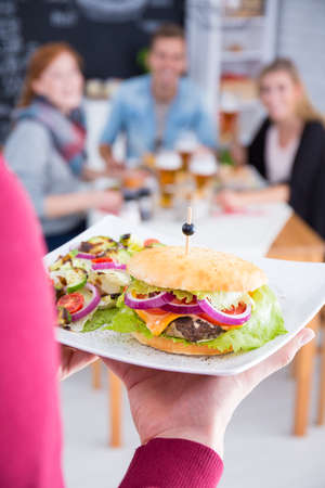 Woman serves a burger with salad on plate in restaurant