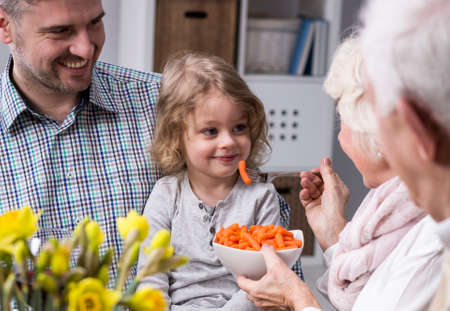 anecdote: Grandmother feeding with healthy carrots grandchild sitting on her fathers lap