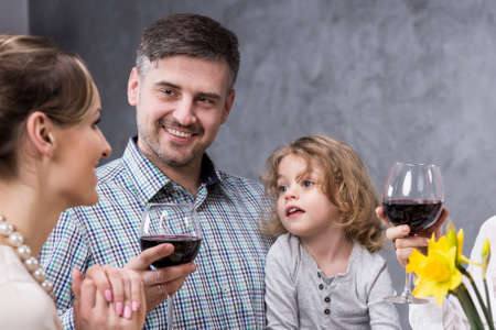 anecdote: Cheerful proud father sitting with his little son with a glass of wine during family meeting