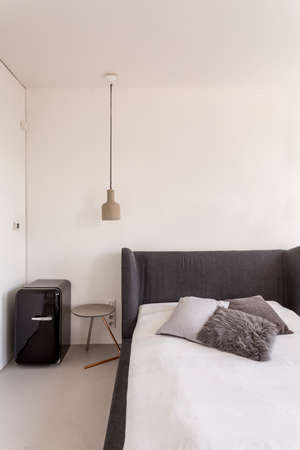 White bedroom with dark grey bed and compact fridge Reklamní fotografie