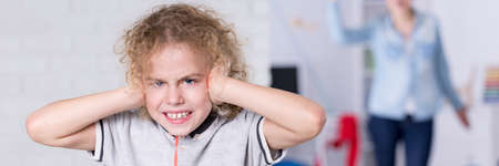 hands covering ears: Angry child covering his ears with his hands Stock Photo