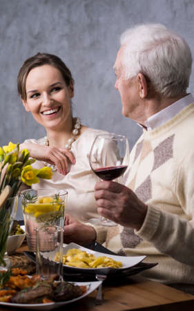 anecdote: Elegant daughter talking with senior father during family dinner in spring