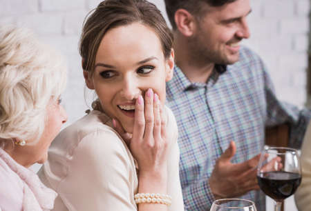 anecdote: Senior mother gossiping with excited daughter during family meeting