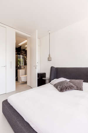 Large bed with white cover in a very bright minimalist scandi bedroom