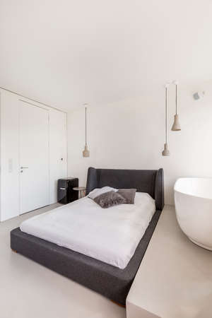 ascetic: White bedroom with simple bed and oval bathtub Stock Photo