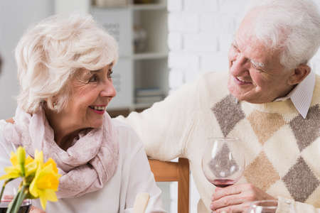 anecdote: Elderly marriage looking at each other with happiness and love during family dinner Stock Photo