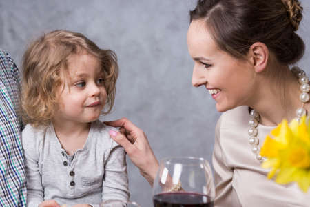 anecdote: Young, pretty woman smiling at her little daughter during dinner