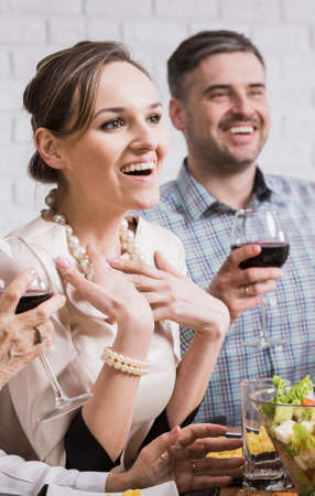 anecdote: Cheerful smiling couple enjoying family dinner with glass of wine