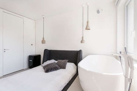 ascetic: Ascetic bedroom with black bed and an oval bathtub Stock Photo
