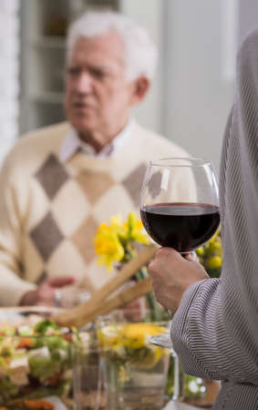 anecdote: Women holding glass with red wine with senior man in the background