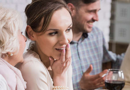 anecdote: Senior woman whispering to her daughter during family meeting