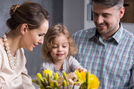 anecdote: Young elegant parents with cheerful child eating family dinner