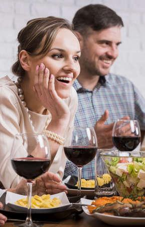 家族との夕食時にワインのグラスをテーブルに座って笑顔のカップル