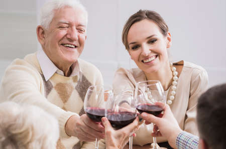 anecdote: Cheerful smiling senior father and daughter making a toast with glasses of wine