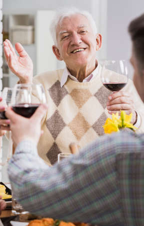 anecdote: Man and elderly father-in-law making a toast with wine during family meeting Stock Photo