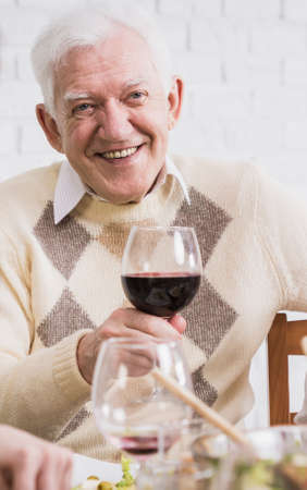 anecdote: Cheerful elderly man making a toast with a glass of red wine Stock Photo