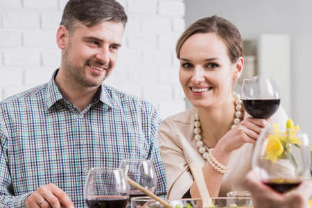 anecdote: Cheerful young couple drinking red wine during meeting