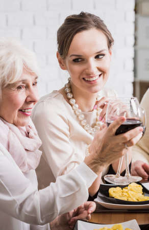 anecdote: Young and senior women sitting at the table and making a tost with wine during family dinner