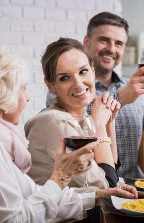 anecdote: Smiling cheerful family making a toast with wine during dinner Stock Photo