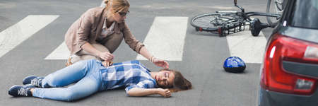 Woman trying to help an unconscious bicyclist lying on a street, panorama Stock Photo