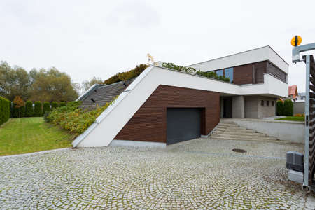 White and brown villa exterior with garden roof