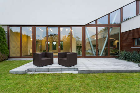 ascetic: Ascetic villa patio with rattan chairs and grey floor Stock Photo