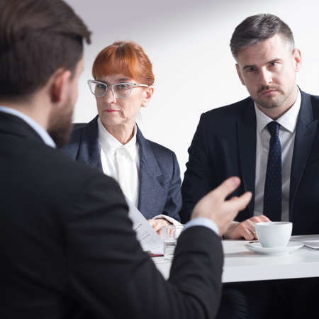 recruiters: Professional recruiters listening to a job applicant in suit Stock Photo