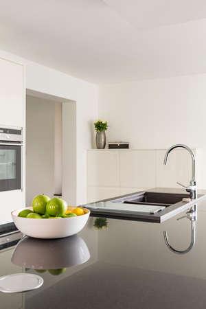 黒のワークトップとシンクの白いキッチン