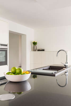 White kitchen with black worktop and sink