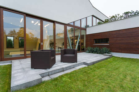 Modern mansion exterior with patio, rattan furniture and window wall