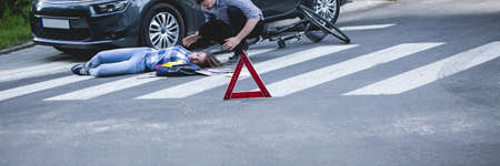 carelessness: Unconscious car accident victim lying on a street and car driver trying to help her, panorama