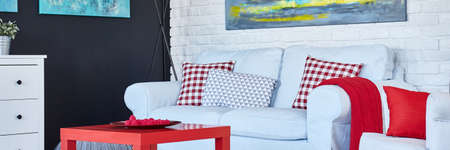 brick wall: Red coffee table and white sofa by the white brick wall