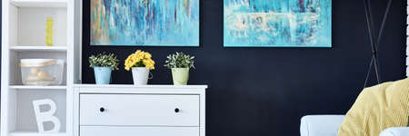 wall paintings: White commode and shelf by the black wall with colorful paintings Stock Photo