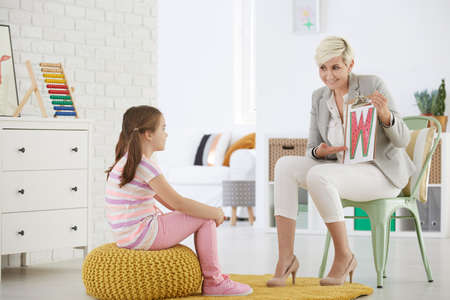 Girl with speech problem learning alphabet with therapist