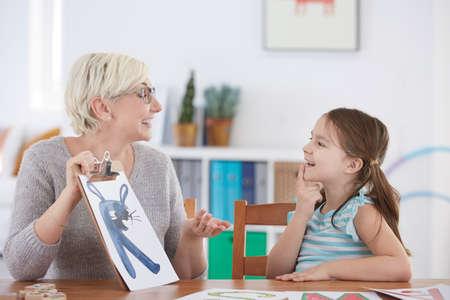 Rede-Spezialist und glückliches Mädchen lernen Alphabet