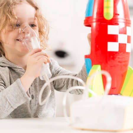 cystic fibrosis: Happy child with oxygen mask playing with toy racket Stock Photo