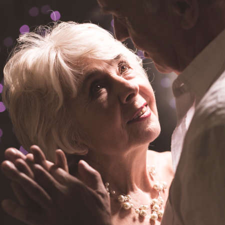 Elder couple dancing and looking at each other with love and trust