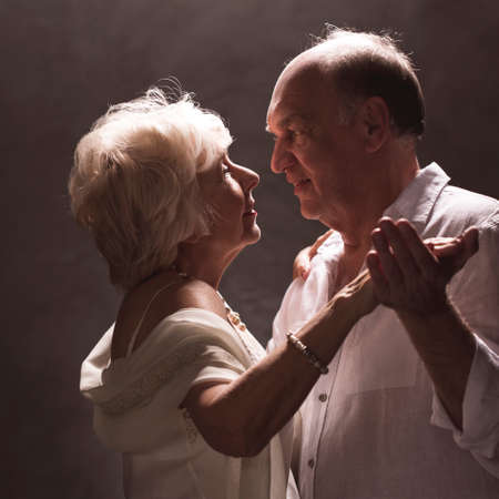 Senior stylish married couple dancing at home