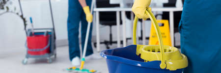 Professional office cleaner is holding a bucket
