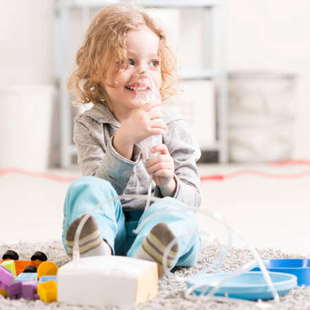 Small girl doing inhalation, sitting on a floor among toys in light interior