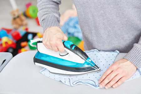 pedant: Close up of young dad ironing baby clothes